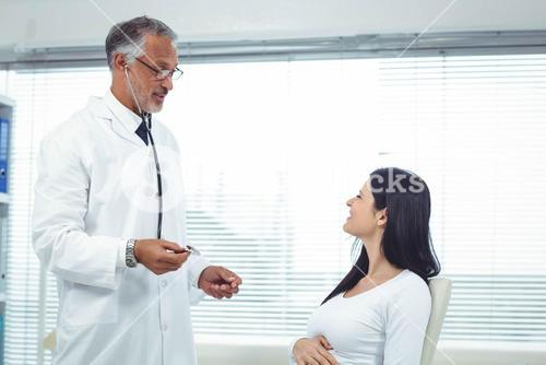 Doctor examining pregnant woman with a stethoscope
