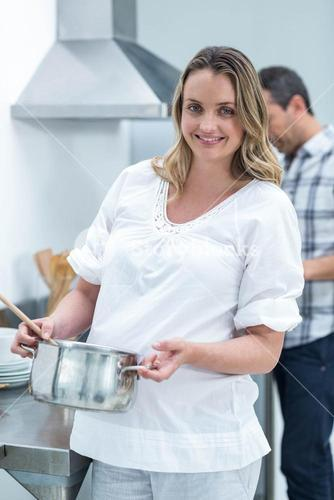 Pregnant woman busy in kitchen