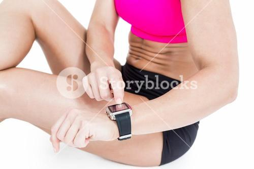Female athlete sitting and using her smart watch
