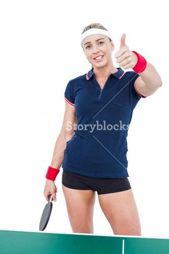 Female athlete playing ping pong and showing thumbs up