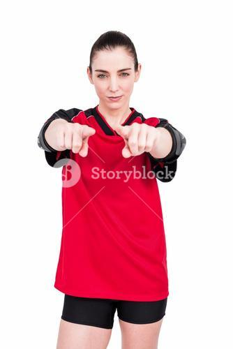 Female athlete posing with elbow pad and pointing the camera