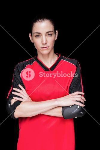 Female athlete posing with elbow pad and crossed arms