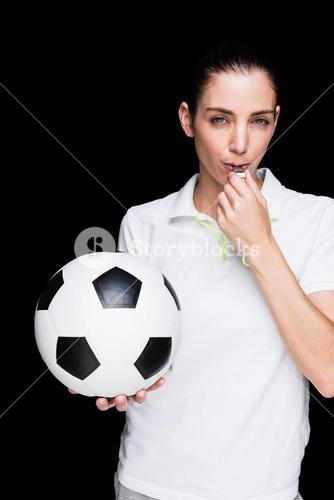 Female athlete blowing a whistle and holding a soccer ball