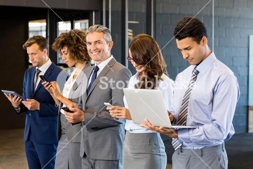 Businesspeople using mobile phone, lap top and digital tablet