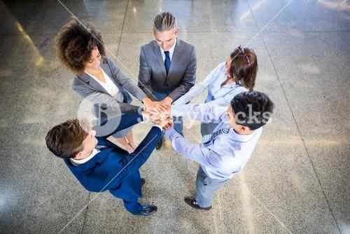 Businesspeople standing with their hands stacked