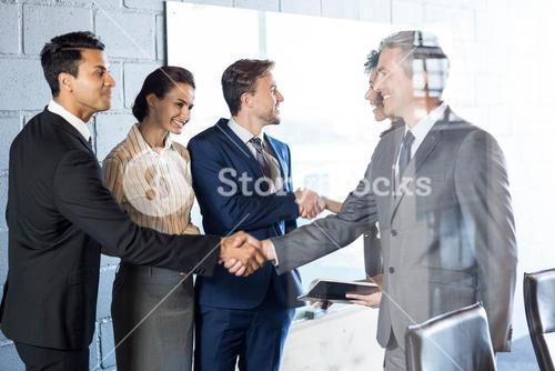 Businessman shaking hands with team
