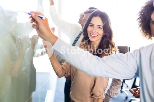 Businesspeople writing on white board