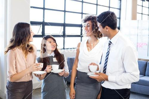 Businesspeople interacting in office during breaktime
