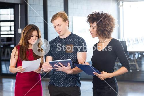 Business executives looking in digital tablet