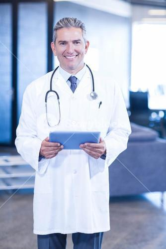 Doctor holding digital tablet and smiling at camera