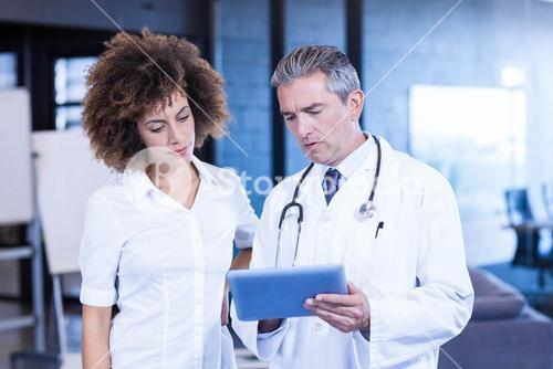 Doctor and colleague looking in digital tablet