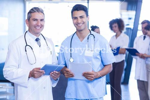 Doctors with digital tablet and medical report looking at camera and smiling
