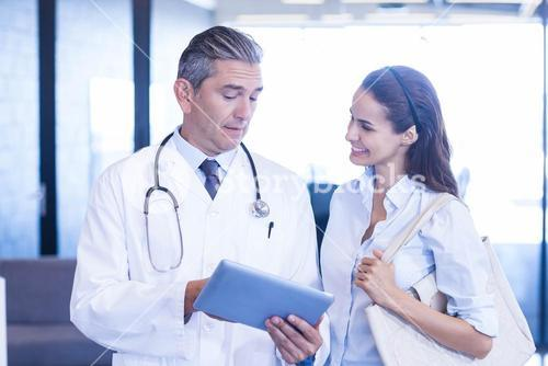 Doctor using digital tablet and having a discussion