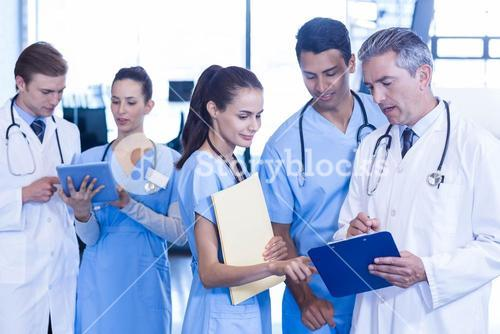 Medical team discussing paperwork on clipboard