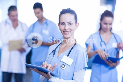 Female doctor using tablet and smiling at camera