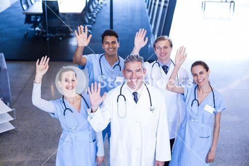Group of medical team standing with their hand raised