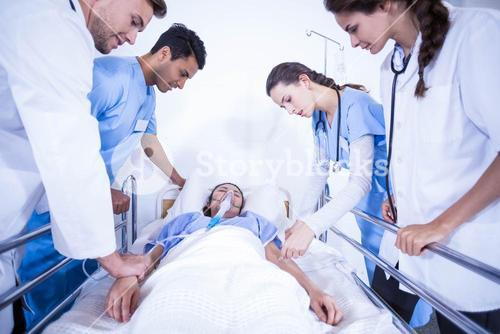 Doctors examining a patient on bed