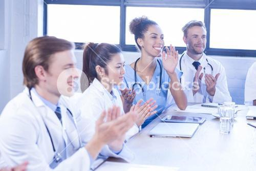 Medical team applauding in meeting