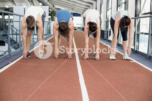 Four athletic women and men stretching
