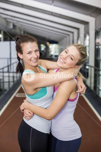 Smiling athletic friends hugging