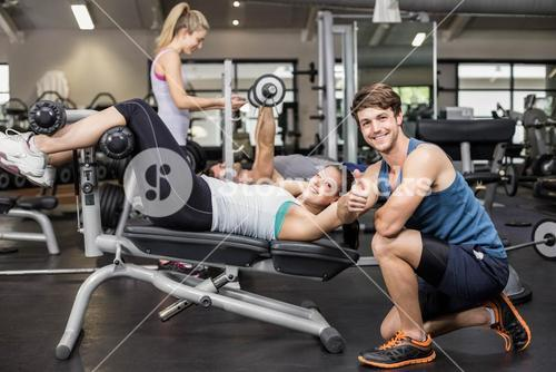 Trainer man helping woman doing her crunches and showing thumbs up