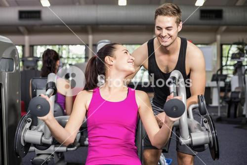 Trainer man helping athletic woman