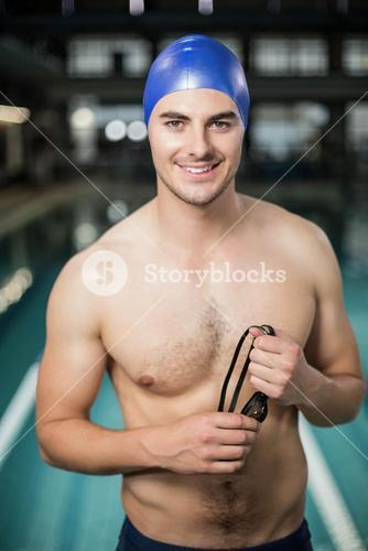 Fit man holding goggles