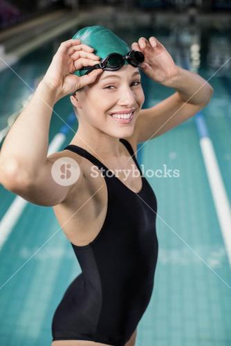 Woman in swimsuit adjusting her goggles