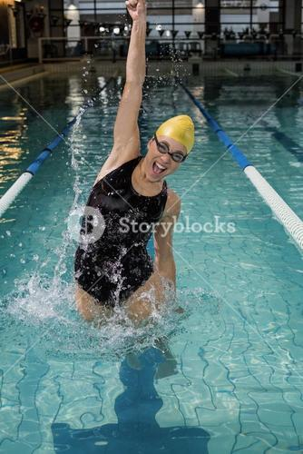 Smiling woman in swimsuit jumping