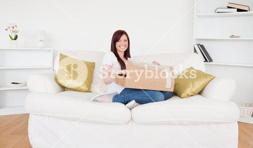 Beautiful redhaired female opening a carboard box while sitting on a sofa