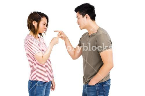 Young couple pointing at each other while having an argument