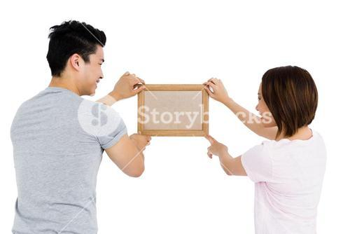 Young couple putting up picture frame