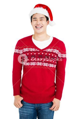 Young man wearing santa hat looking at camera and smiling