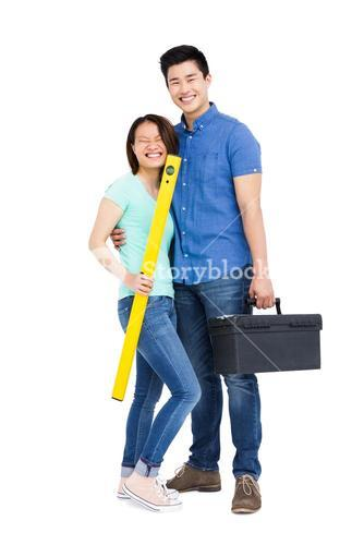 Young couple standing with spirit level measuring tool and tool box