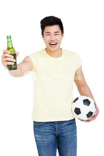 Fan holding a beer bottle and football