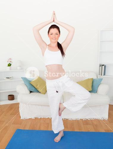 Attractive redhaired woman stretching in the living room