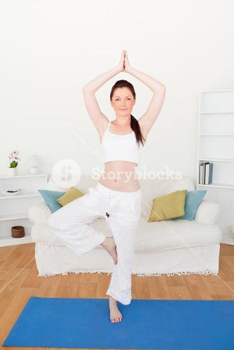 Beautiful redhaired woman stretching in the living room