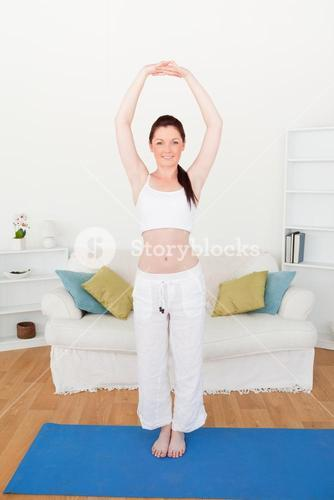 Good looking redhaired woman stretching in the living room
