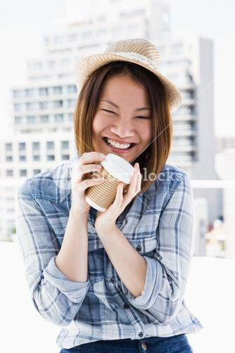 Young woman holding disposable cup
