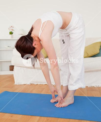 Beautiful redhaired female stretching in the living room