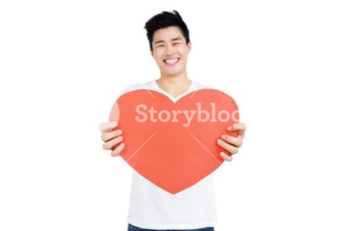Young man holding heart shape
