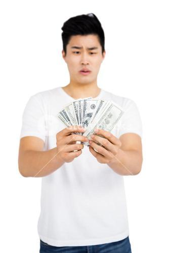 Upset young man counting fanned out currency notes