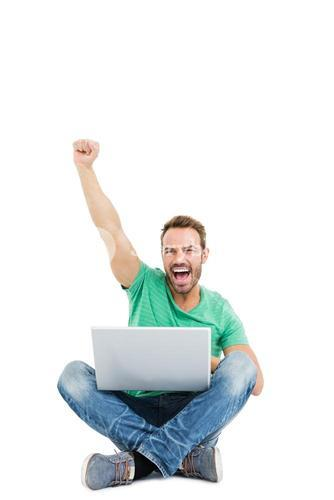 Happy young man raising his fist while using laptop