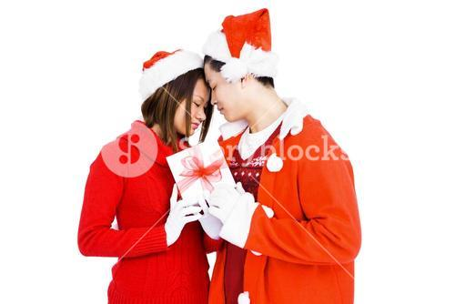 Young couple in christmas attire holding gift