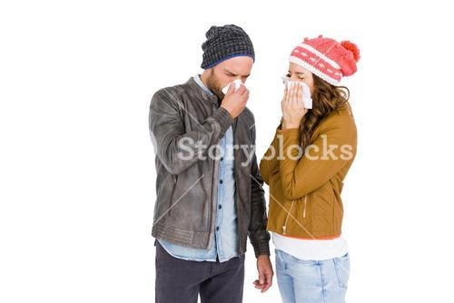 Sick young couple blowing nose