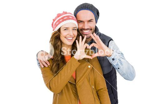 Happy young couple making heart gesture