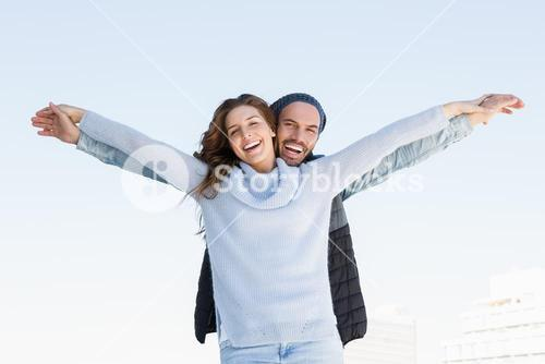 Happy couple standing with arms outstretched