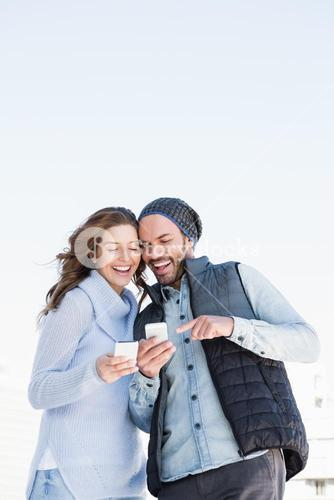 Happy young couple using mobile phone