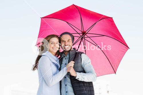 Happy young couple holding pink umbrella
