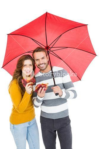 Happy young couple holding umbrella